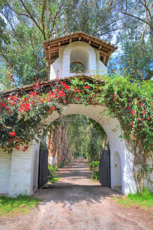Entrance to an old hacienda converted to a public  restaurant, with a tower, gate, flowers and an old dirt road, Pichincha Province, Ecuador. Stock Photo