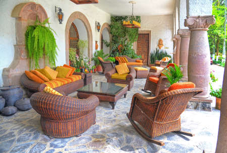 Outdoor sitting room with chairs, seats, couches and tables, decorated with plants, arches and old pottery. Outskirts of Quito, Pichincha, Ecuador. Stock Photo