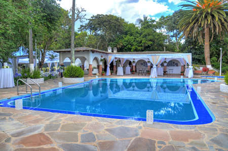 Large swimming pool with neighboring bushes, plants, trees, buildings, stone floors, at an hacienda turned to a restaurant. Outskirts of Quito, Pichincha, Ecuador.