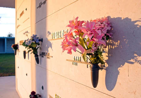 Plastic Flowers In Vases Hanging From Cemetery Niches At A Local
