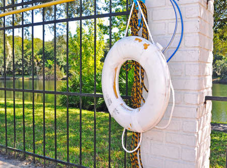 White life buoy for safety hanging from a wall nearside a swimming pool with a lake in the background. Tampa, Florida, USA. Фото со стока - 84655692