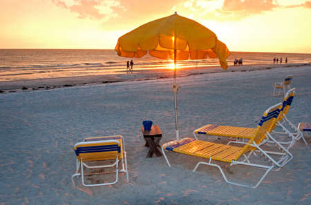 Beach chairs and parasol umbrella on the sand in front of the ocean at sunset, Clearwater Beach, Florida, USA.