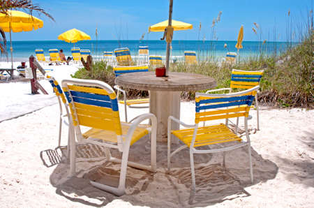 Beach chairs and table on the beach sand on a sunny morning, Clearwater Beach, Florida, USA. Фото со стока