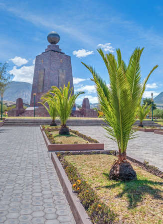 View of the Middle of the World monument with a palm tree in the foreground, on a sunny summer morning. Ecuador. Mitad del Mundo.