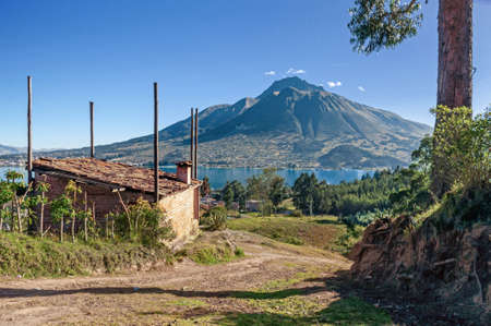 View of the Imbabura volcano, San Pablo lake, surrounding fields and a small cabin, on a clear morning. Ecuador