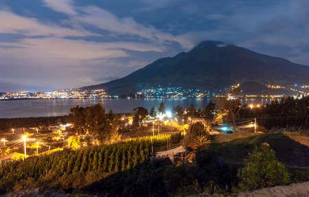 San Pablo lake, Imbabura volcano and surrounding towns, at night. Ecuador Фото со стока