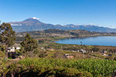Beautiful view of the San Pablo lake, with surrounding houses and towns, and the Cotacachi volcano in the background, on sunny and bright morning. Ecuador South America