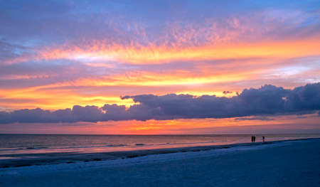 Beautiful cloudy sunset at Siesta Key, with people in silhouette in the foreground.