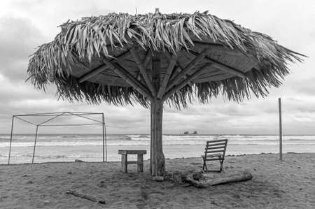 Beach parasol and lounge chair of a fishing town, in front of the ocean, in black and white. Ayampe beach, Manabi, Ecuador Stock fotó