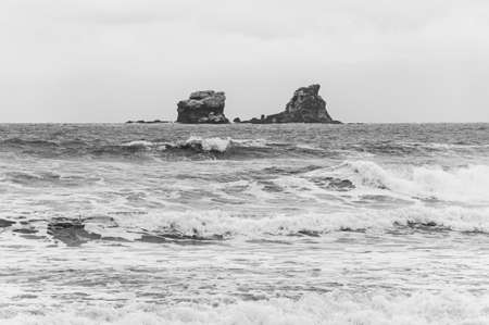 Two rock island formations in the middle of the ocean, in front of the town of Ayampe, Manabi, on an overcast and rainy morning. Ecuador