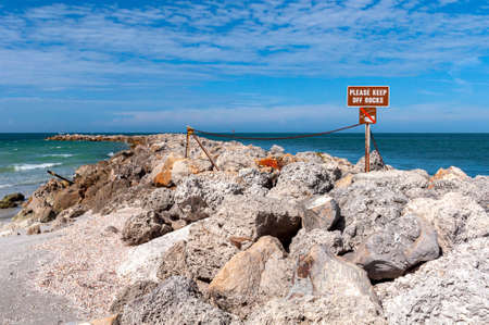 Please Keep of the Rocks sign, on a rock barrier wall at the north end of Bell Air Beach, Florida, USA Reklamní fotografie