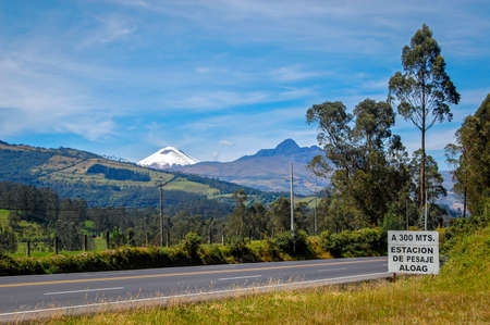 View of a highway, with a sign for next toll, surrounded by trees and the Cotopaxi volcano in the background