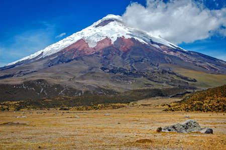 View of the Cotopaxi volcano on a sunny morning, with volcanic rocks in the foreground. Cotopaxi National Park, Ecuador