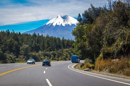 Highway south towards the Cotopaxi volcano, with traveling vehicles, on a sunny morning, Ecuador.