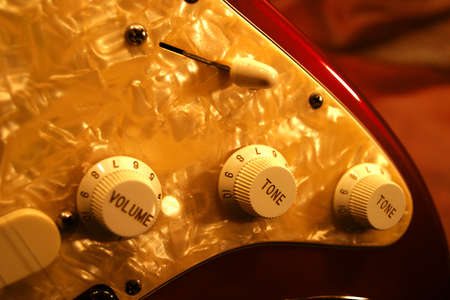 selector: Tone and volume knobs and pickup selector of a modern solid body electric guitar.