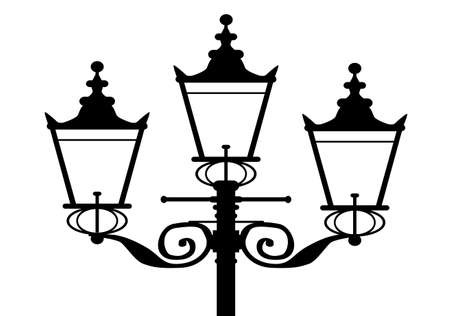 A typical old London gas street light in silhouette