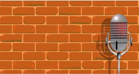 comedian: A microphone ready on stage against a brick wall