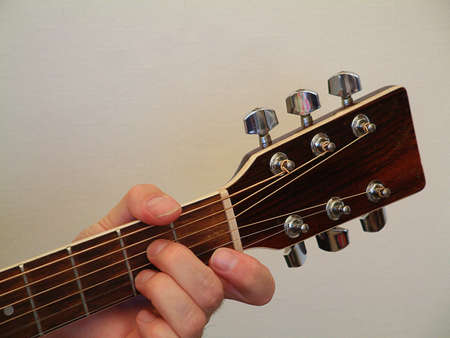 fingering: The hand of a guitarist on the neck of an acoustic guitar