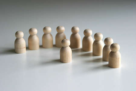 work force: A collection of Wooden peg figures in semi circle with one central figure Stock Photo