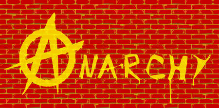 The word anarchy painted onto a red brick wall in yellow paint