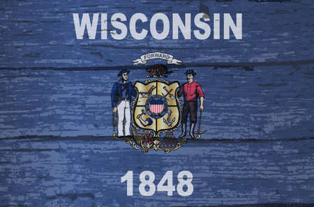 The flag of the USA state of Wisconsin on a wooden background Фото со стока