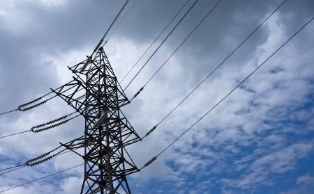 voltage gray: Pylon of power transmission line against the background of a cloudy sky Stock Photo