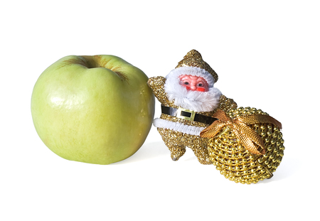Toy Santa Claus with an apple and a gold ball. Isolated on white background. photo