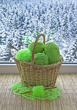 Green skeins and crochet hooks are in the basket  photo