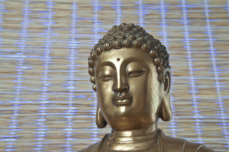 Head of golden Buddha which looks down is on the mat background photo