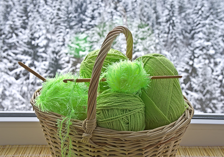 Green skeins and crochet hooks are in the basket on background snowy forest photo