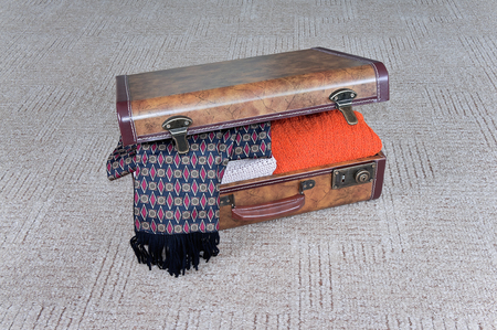 leathern: Outdated leathern ajar suitcase with clothing lies on the carpet