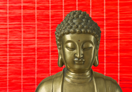 Head of golden Buddha which looks down is on the red background photo