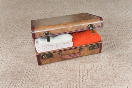 leathern: Outdated leathern suitcase full of clothing lies on the carpet