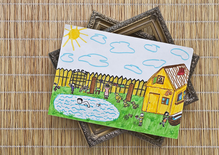A children s drawing painted colors and picture frames are on a wicker mat