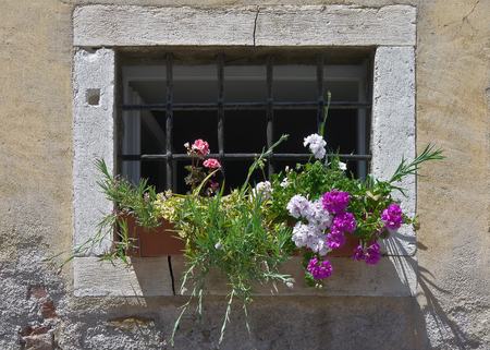 Ornamental flowerpot with flowers is before the barred window of an old house photo