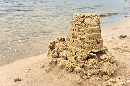 Child has done on the river bank cake of the wet sand