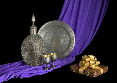 Silverware is on the draped violet fabric and the gift with a bow  Black background  photo