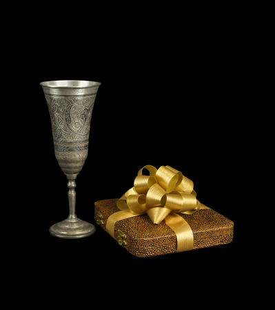 The silver goblet and the gift with a bow isolated on black background  photo
