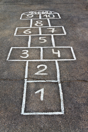 Cells for game hopscotch drawn with chalk on the pavement photo