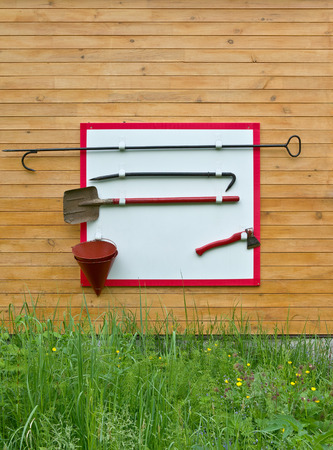 extinguish: Shield with the tools to extinguish the fire hanging on a wooden wall