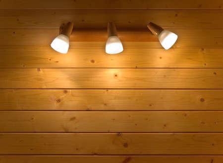 wall sconce: Candelabro el�ctrico con tres l�mparas brillantes que cuelgan en la pared de madera Foto de archivo