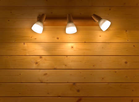 sconce: Electric sconce with three glowing lamps hanging on the wooden wall