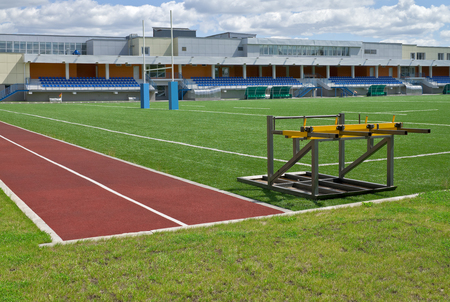compacting: Equipment for compacting of grass on rugby field and empty grandstand stadium