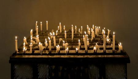 sanctity: Masterizzazione di candele � su uno sfondo marrone scuro Archivio Fotografico