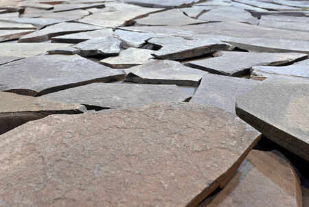 depth of field: Cobbled pavement of of shapeless stone slabs. Small depth of field.