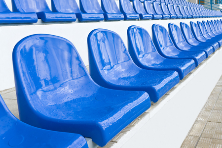 Empty plastic chairs are on grandstand stadium.Small depth of field.