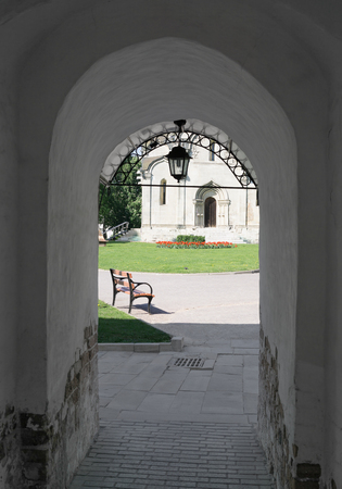 ecclesiastical: Temple of Christian monastery, bench and lamp through archway Stock Photo