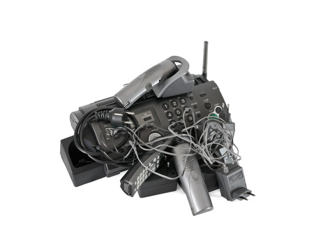 cable tangle: Heap of cordless telephones, cables and modem isolated on white background