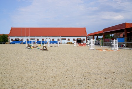 grandstand: Empty field  for show jumping and grandstand against the background of stable