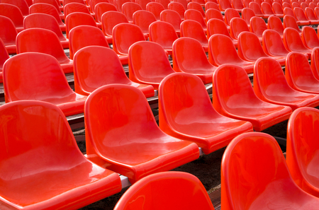 Empty plastic chairs of red color are on grandstand stadium